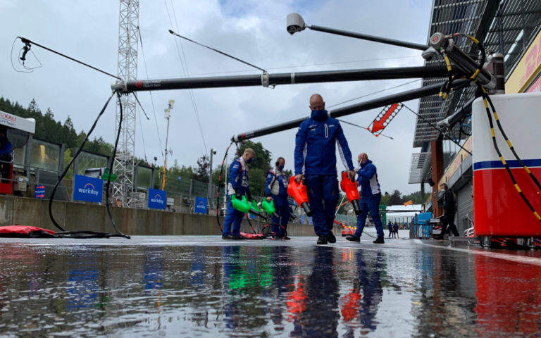 Mechanici Haasu fukármi sušia asfalt pred garážou, dážď