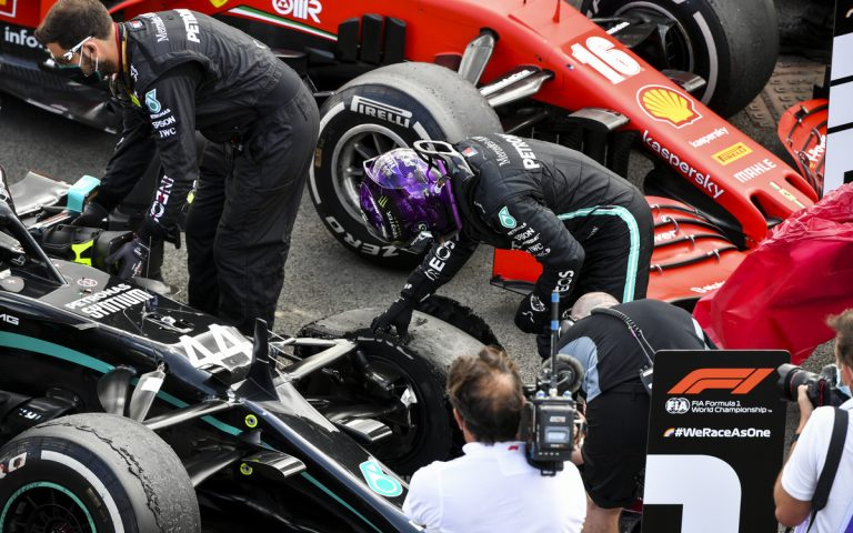Lewis Hamilton skúma zničenú pneumatiku
